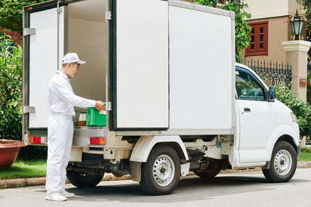 Delivery man in white uniform taking plastic crate with glass milk bottles out of van trunk
