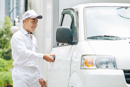 Handsome smiling young Asian delivery man in white suit and cap opening van door