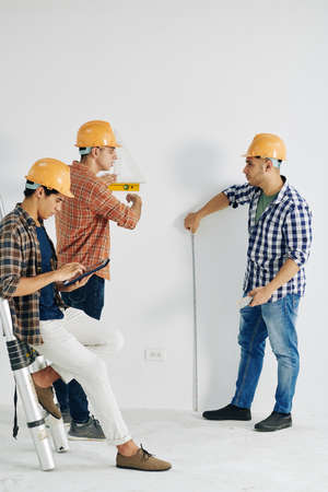 Construction workers measuring wall with various tool when their colleague enterring data in document on tablet computer