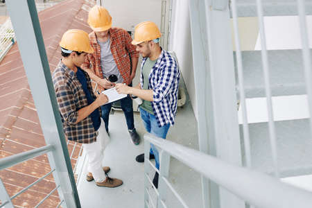 Young builders drinking morning cafe and checking plan of works on tablet computer Foto de archivo