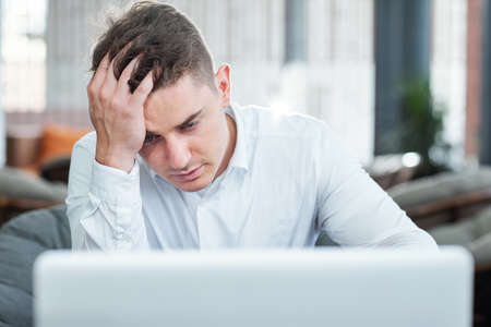Stressed and tired young businessman did not save the document he was working on all day long