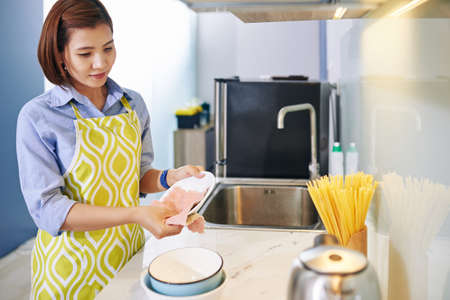 Pretty young Vietnamese housewife wiping plates with soft cloth after finishing cooking
