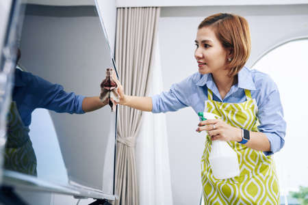 Positive young Asian woman wiping dust off television screen with soft cloth