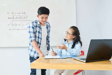 Smiling mature math teacher explaining difficult topic to confused schoolboy after class