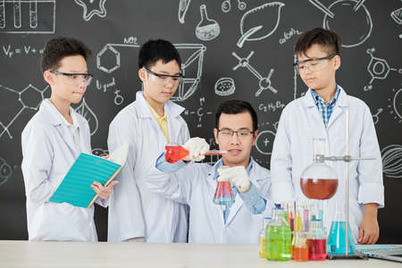 Group of curious Vietnamese students in labcoats and goggles looking at their teacher mixing reagents in beaker