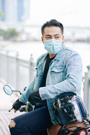 Portrait of handsome motorcyclist in medical mask sitting on bike and looking away