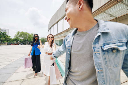 Cheerful young Vietnamese man pulling hand of girlfriend and her friend with shopping bags who spent all the money in mall
