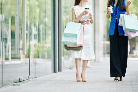 Cropped image of elegant young women drinking take away coffee when walking outdoors after shopping Stock Photo