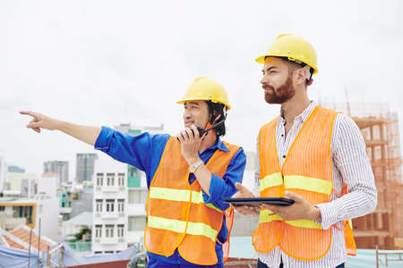Smiling Vietnamese contractor talking on walkie-talkie and pointing away when standing next to head engineer with digital tablet in hands