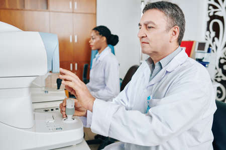 Opthalmologist using non-mydriatic fundus camera when examining patient