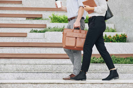 Cropped image of businessman and businesswoman with take away coffee walking outdoors