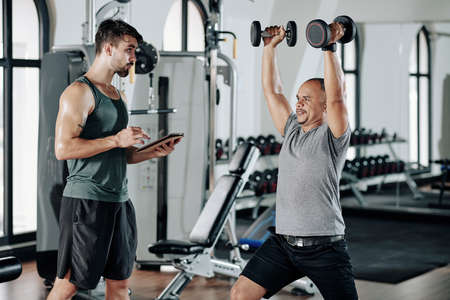 Fitness trainer taking notes in document on tablet computer when his client raising arms with heavy dumbbells and doing lunges