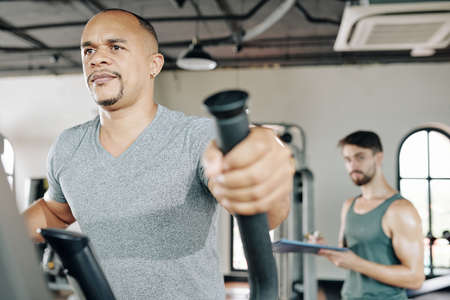 Mature serious man walking on elliptical machine in gym, his personal trainer looking in background
