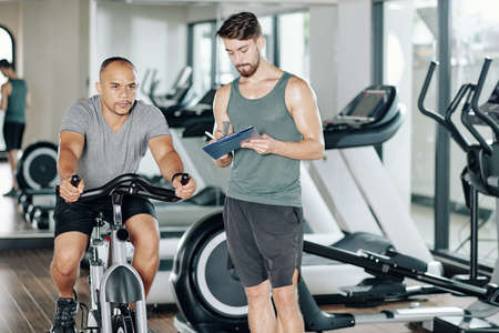 Fitness trainer writing in document when his client trying new cardio workout and riding fast on stationary bicycle Reklamní fotografie