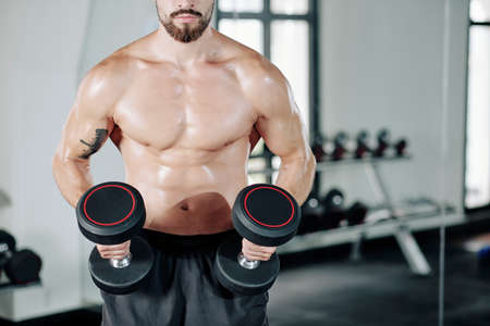 Cropped image of shirtless muscular man standing in gym with two heavy dumbbells
