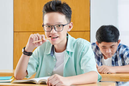Portrait of smart Vietnamese school student sitting at desk with opened book and chewing pencil