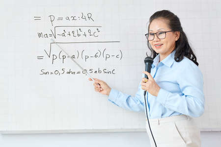 Math teacher speaking in microphone when pointing at equation on whiteboard and explaining new topic to students