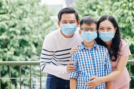 Cheerful Asian family of three in medical masks standing outdoors and looking at camera