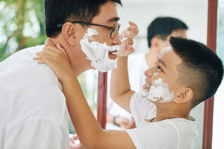 Happy preteen son putting shaving cream on nose of his father when are getting ready together in the morning