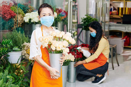 Portrait of senior florist standing in store with metal bucket of white roses, her daughter spraying flowers in background