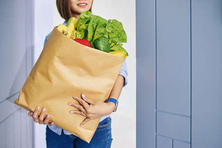 Smiling housewife bringing big package with fresh groceries to home