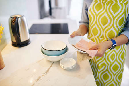 Cropped image of woman wiping dishware with cotton towel in kitchen
