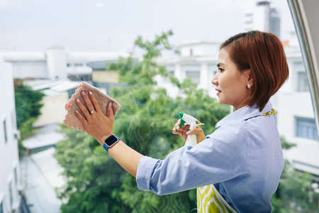 Asian housewife in smartwatch wiping window with cleaning spray Imagens