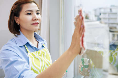 Smiling pretty young Asian woman in apron cleaning window in her apartment