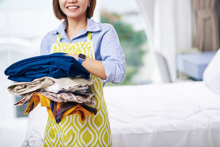 Cropped image of smiling housewife in apron holding pile of clothes ready for ironing