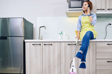 Vietnamese housewife with vacuum cleaner in hand sitting on kitchen counter and talking on phone with friend
