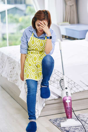 Depressed housewife in apron sitting on bed edge tired after vacuum cleaning her apartment