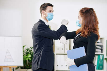 Business people in medical masks and rubber gloves doing elbow bump due to coronavirus pandemic when greeting each other before meeting