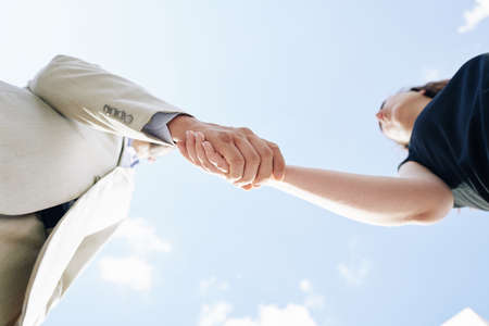 Business partners shaking hands and greeting each other, view from below