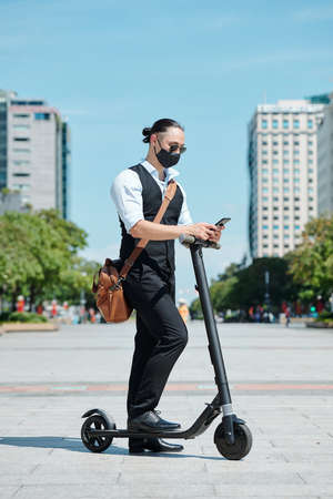 Young entrepreneur in protective mask standing on scooter and reading text messages on smartphone