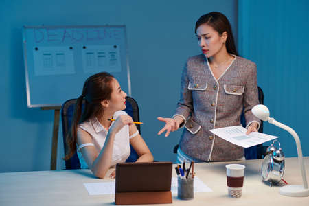 Irritated young businesswoman talking to UI designer and telling her off for working slow on night before deadline