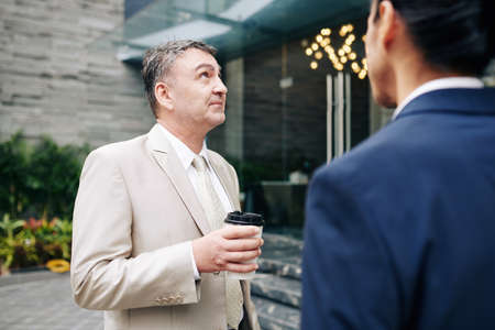 Pensive aged entrepreneur drinking morning coffee with his coworker and looking at office building they are working at
