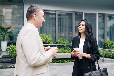 Smiling beautiful young Asian businesswoman listening to ideas of her senior colleague when they are drinking take out coffee outdoors