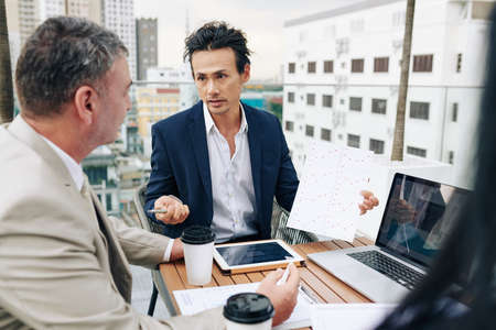 Entrepreneur showing chart to his coworkers when they are having meeting on rooftop