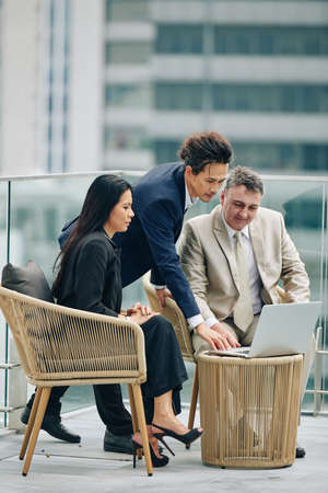 Multi-ethnic business people reading report on laptop whne having meeting on rooftop