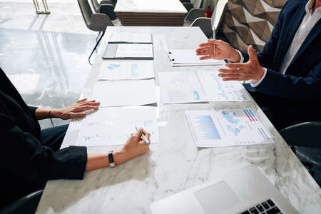Cropped image of business people analyzing various charts and reports at meeting