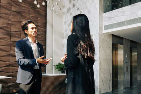 Serious mixed-race businessman talking to female entrepreneur in lobby of office building