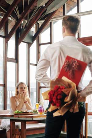 Excited young woman looking at boyfriend with box of chocolate and flowers coming to her table