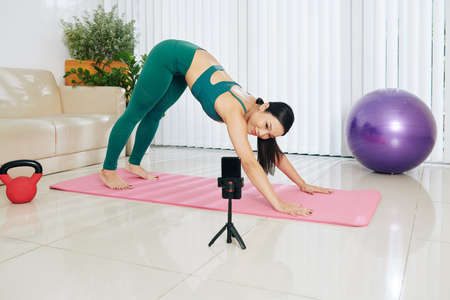 Smiling pretty Asian fintess blogger conducting online yoga class for her subscribers and doing downward facing dog pose in front of smartphone