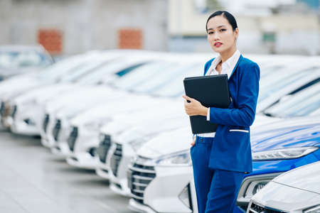 Portrait of confident successful saleswoman with leather folder in hands standing in car dealership