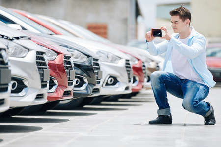 Car dealershop worker photographing cars for social media account 免版税图像 - 156760217