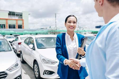 Smiling pretty Vietnamese car dealership saleswoman in suit shaking hand of customer 免版税图像