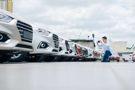 Young man in casual clothes photographing rows of cars in car dealership parking
