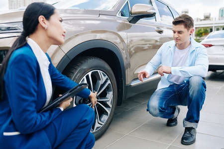 Young man asking saleswoman questions about alloy wheels of car he is going to buy 免版税图像