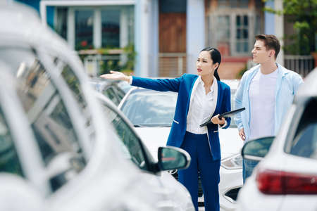 Female manager helping client to choose car in rental service parking