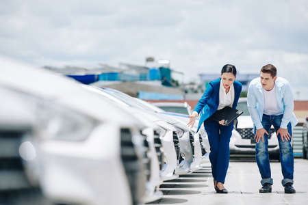 Female car dealership manager showing new vehicles to male client and helping him to choose one